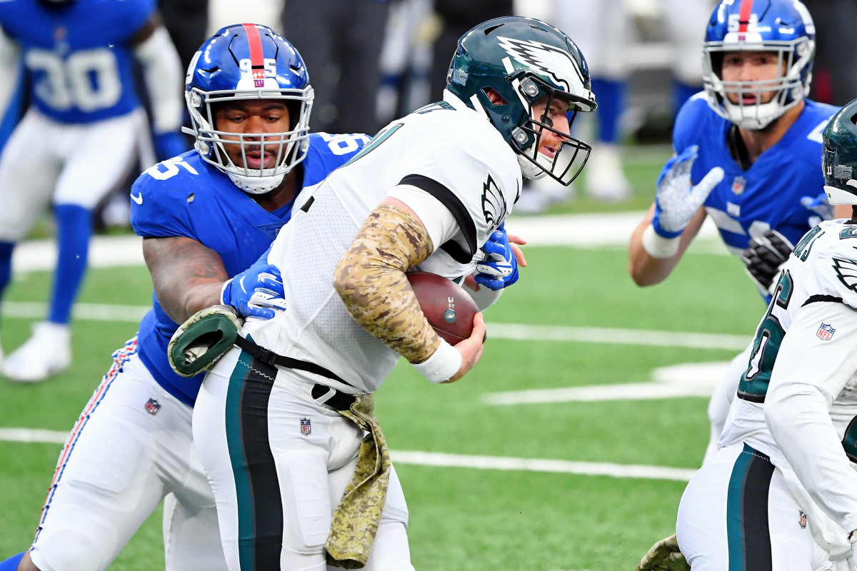 Nov 15, 2020; East Rutherford, New Jersey, USA; New York Giants defensive tackle B.J. Hill (95) tackles Philadelphia Eagles quarterback Carson Wentz (11) for a loss of yards during the first half at MetLife Stadium.