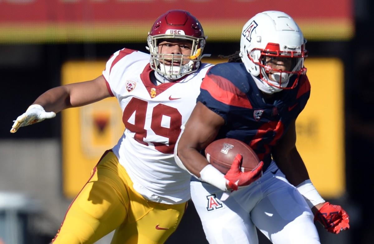 Nov 14, 2020; Tucson, Arizona, USA; USC Trojans defensive lineman Tuli Tuipulotu (49) pursues Arizona Wildcats running back Gary Brightwell (0) during the first half at Arizona Stadium.