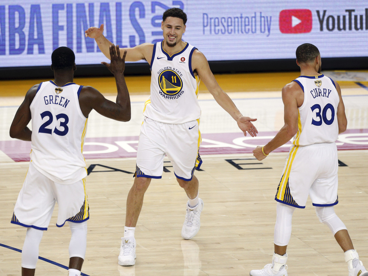 Golden State Warriors guard Klay Thompson (11) reacts with forward Draymond Green (23) and guard Stephen Curry (30) during overtime in game one of the 2018 NBA Finals at Oracle Arena.