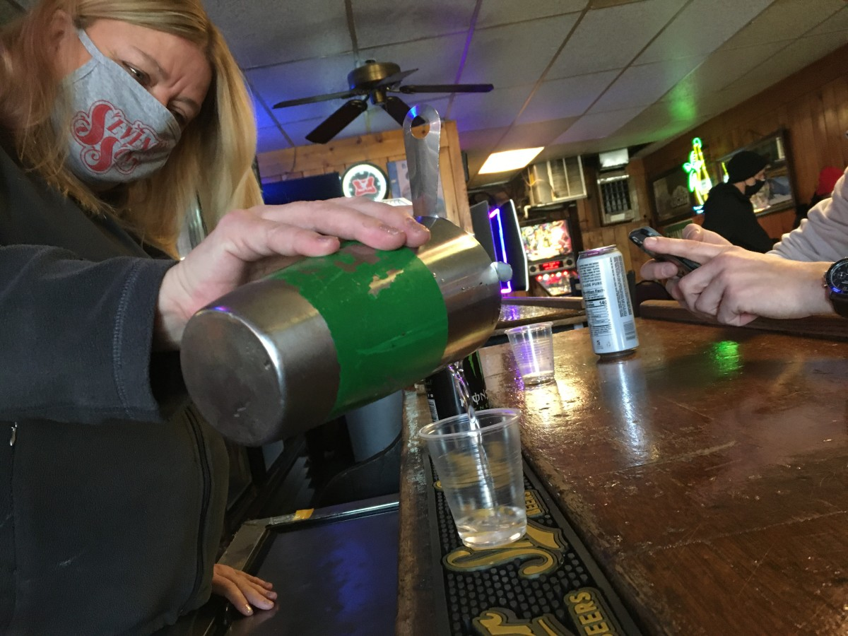 Sharon Lyons, a bartender at Mike's in Columbus, pours a shot for her regular customers on Thursday morning