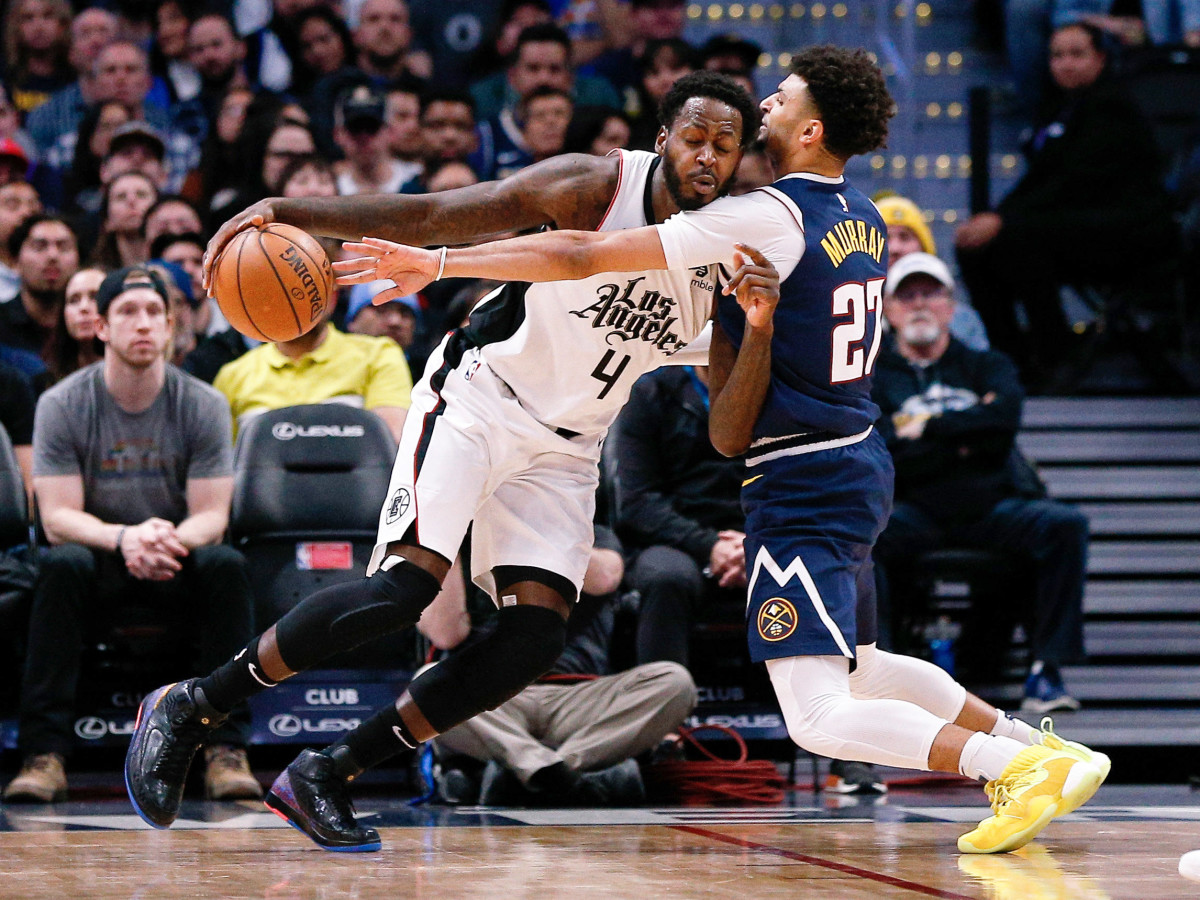 Jan 12, 2020; Denver, Colorado, USA; Los Angeles Clippers forward JaMychal Green (4) controls the ball as Denver Nuggets guard Jamal Murray (27) guards in the second quarter at the Pepsi Center.