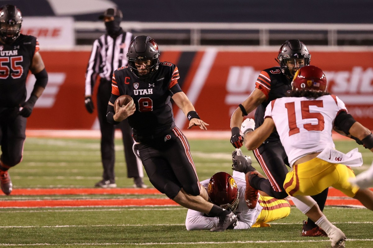 Nov 21, 2020; Salt Lake City, Utah, USA; Utah Utes quarterback Jake Bentley (8) is tackled by USC Trojans linebacker Hunter Echols (31) while running up the field during the second half at Rice-Eccles Stadium. USC Trojans won 33-17.