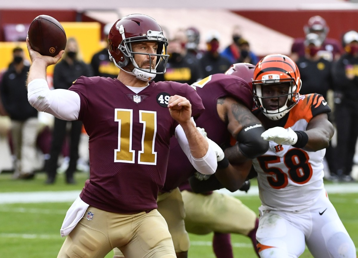 Nov 22, 2020; Landover, Maryland, USA; Washington Football Team quarterback Alex Smith (11) throws a pass as Cincinnati Bengals defensive end Carl Lawson (58) rushes during the second half at FedExField.