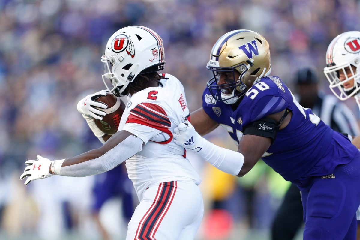 Nov 2, 2019; Seattle, WA, USA; Washington Huskies linebacker Zion Tupuola-Fetui (58) drags down Utah Utes running back Zack Moss (2) during the second quarter at Husky Stadium.