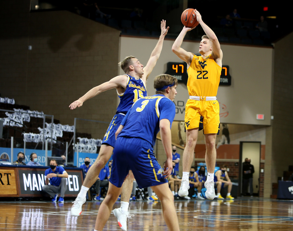 SIOUX FALLS, SD - NOVEMBER 25: Sean McNeil #22 of the West Virginia Mountaineers shoots a jumper over Noah Freidel #15 of the South Dakota State Jackrabbits during the Bad Boy Mowers Crossover Classic at the Sanford Pentagon in Sioux Falls, SD.