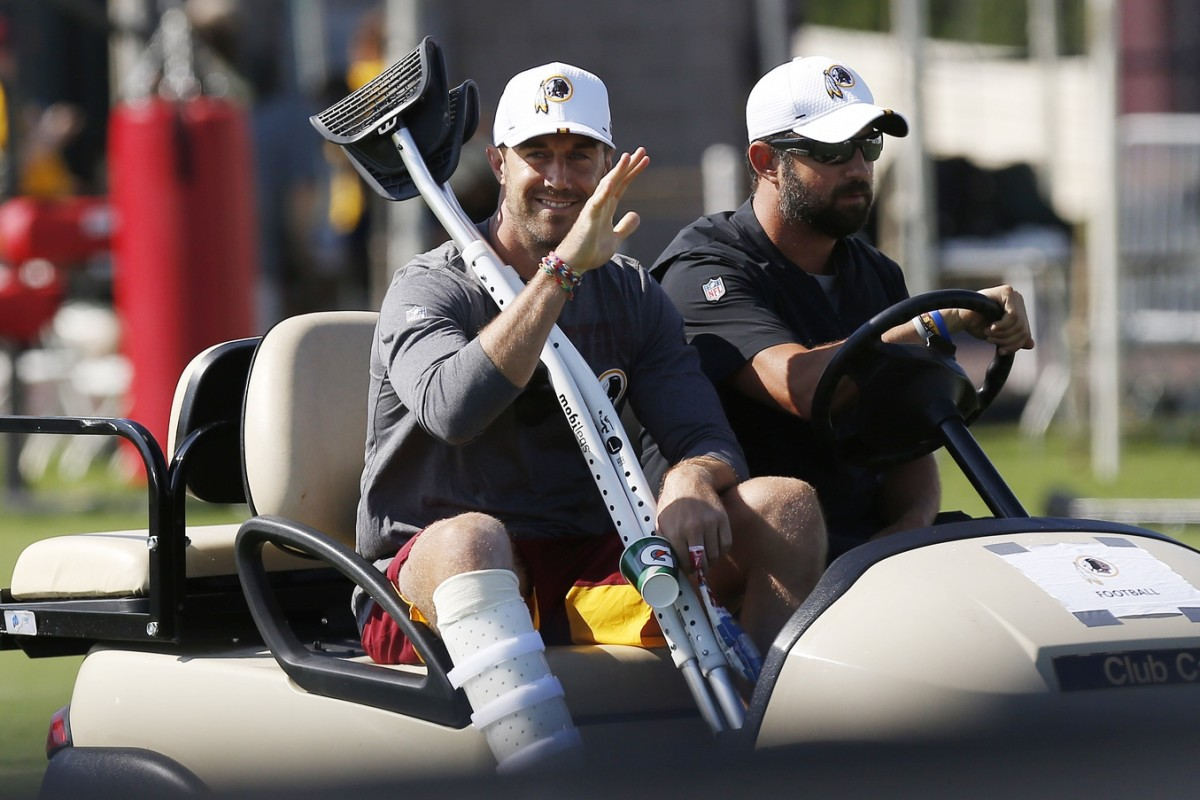 Jul 25, 2019; Richmond, VA, USA; Injured Washington Redskins quarterback Alex Smith (R) waves to fans while riding a golf cart prior to day one of Redskins training camp at Bon Secours Washington Redskins Training Center.