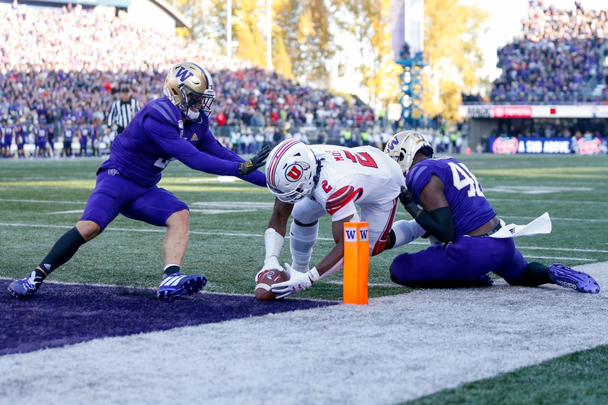 Nov 2, 2019; Seattle, WA, USA; Utah Utes running back Zack Moss (2) dives into the end zone for a touchdown as Washington Huskies defensive back Elijah Molden (left) and linebacker Edefuan Ulofoshio (right) try to stop him during the second quarter at Husky Stadium.