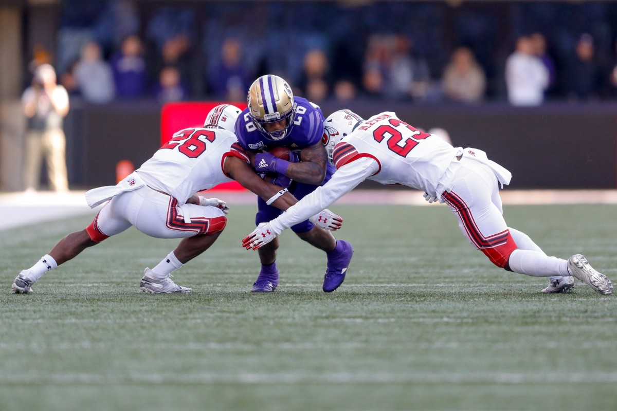 Nov 2, 2019; Seattle, WA, USA; Utah Utes defensive back Terrell Burgess (26) and defensive back Julian Blackmon (23) combine to tackle Washington Huskies running back Salvon Ahmed (26) during the first quarter at Husky Stadium.