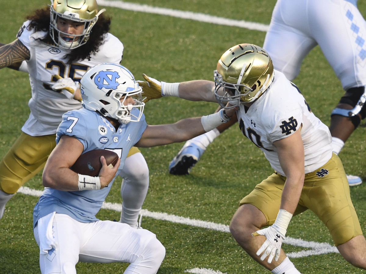 North Carolina Tar Heels quarterback Sam Howell (7) is sacked by Notre Dame Fighting Irish linebacker Marist Liufau (35) and linebacker Drew White (40) in the second quarter at Kenan Memorial Stadium.