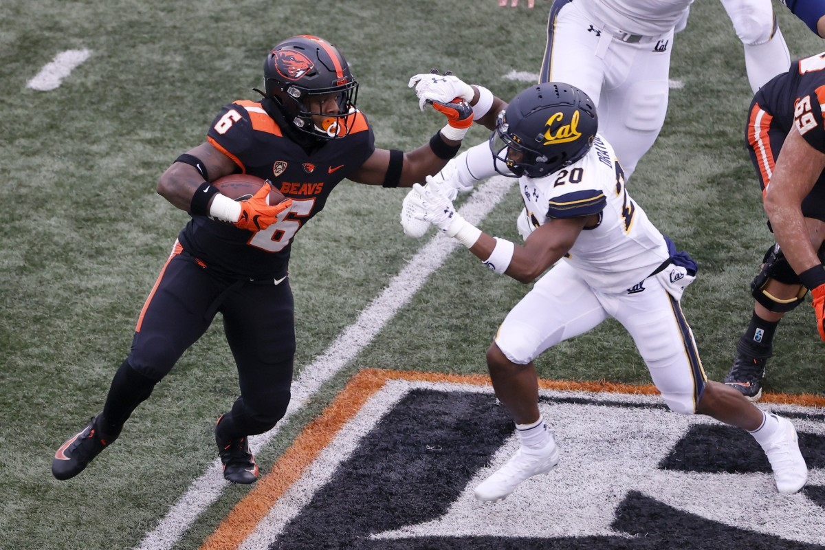 Nov 21, 2020; Corvallis, Oregon, USA; Oregon State Beavers running back Jermar Jefferson (6) is defended by California Golden Bears corner back Josh Drayden (20) during the first half at Reser Stadium.