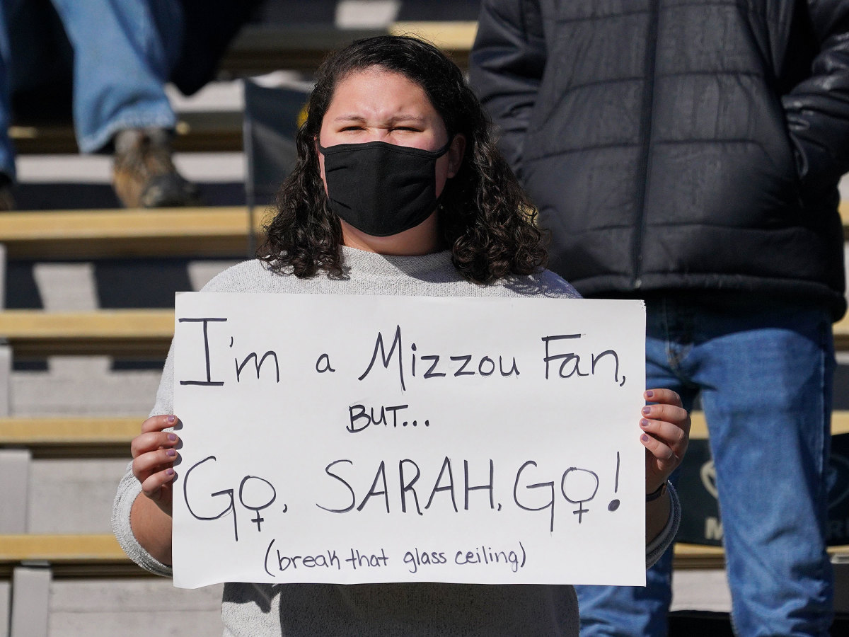 "A fan holds a sign that says ""I'm a Mizzou Fan But....Go, Sarah, Go!"""