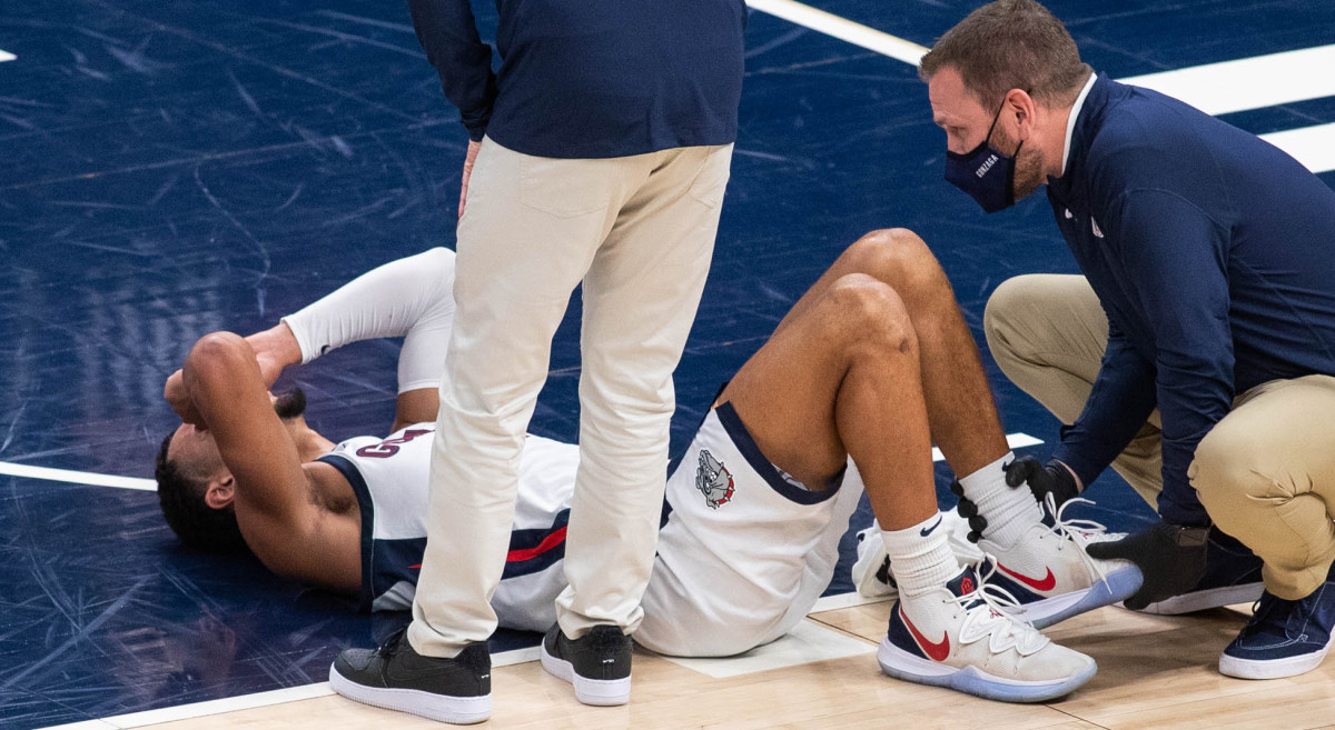 Gonzaga Bulldogs guard Jalen Suggs (1) lies down on the floor after suffering an apparent injury against the West Virginia Mountaineers in the first half at Bankers Life Fieldhouse.
