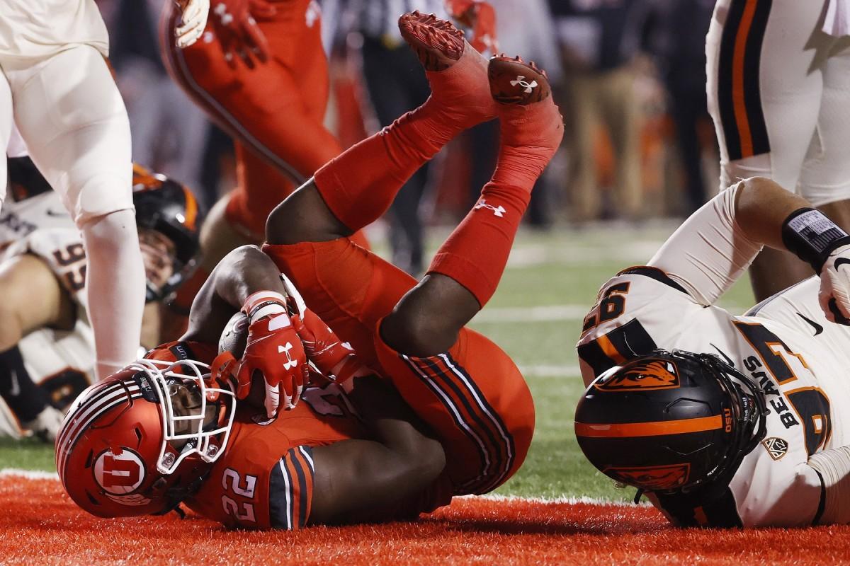 Dec 5, 2020; Salt Lake City, Utah, USA; Utah Utes running back Ty Jordan (22) runs for a touchdown against Oregon State Beavers defensive lineman Alexander Skelton (97) in the second quarter at Rice-Eccles Stadium.
