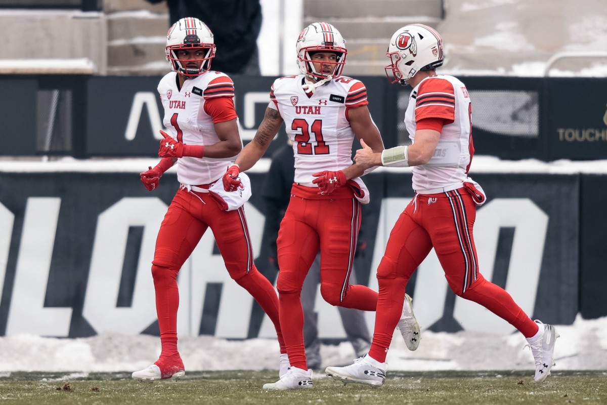 Dec 12, 2020; Boulder, Colorado, USA; Utah Utes wide receiver Solomon Enis (21) celebrates his touchdown with quarterback Jake Bentley (8) and wide receiver Bryan Thompson (1) in the first quarter against the Colorado Buffaloes at Folsom Field.