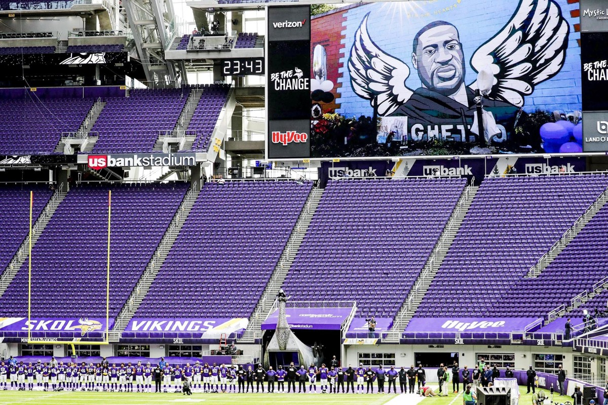 A mural of George Floyd on the video screen and a stadium full of empty seats at the Vikings' season opener