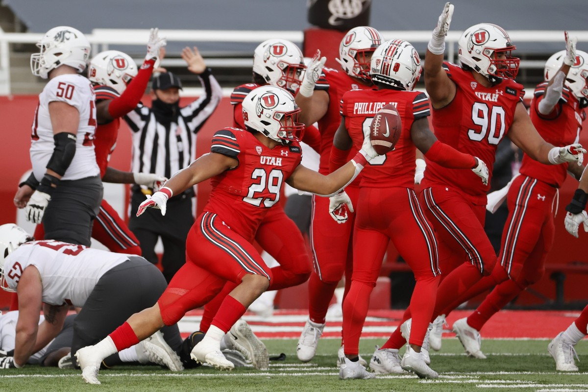 Dec 19, 2020; Salt Lake City, Utah, USA; Utah Utes linebacker Nephi Sewell (29) celebrates a fumble recovery in the fourth quarter by Washington State Cougars wide receiver Travell Harris (1) at Rice-Eccles Stadium.