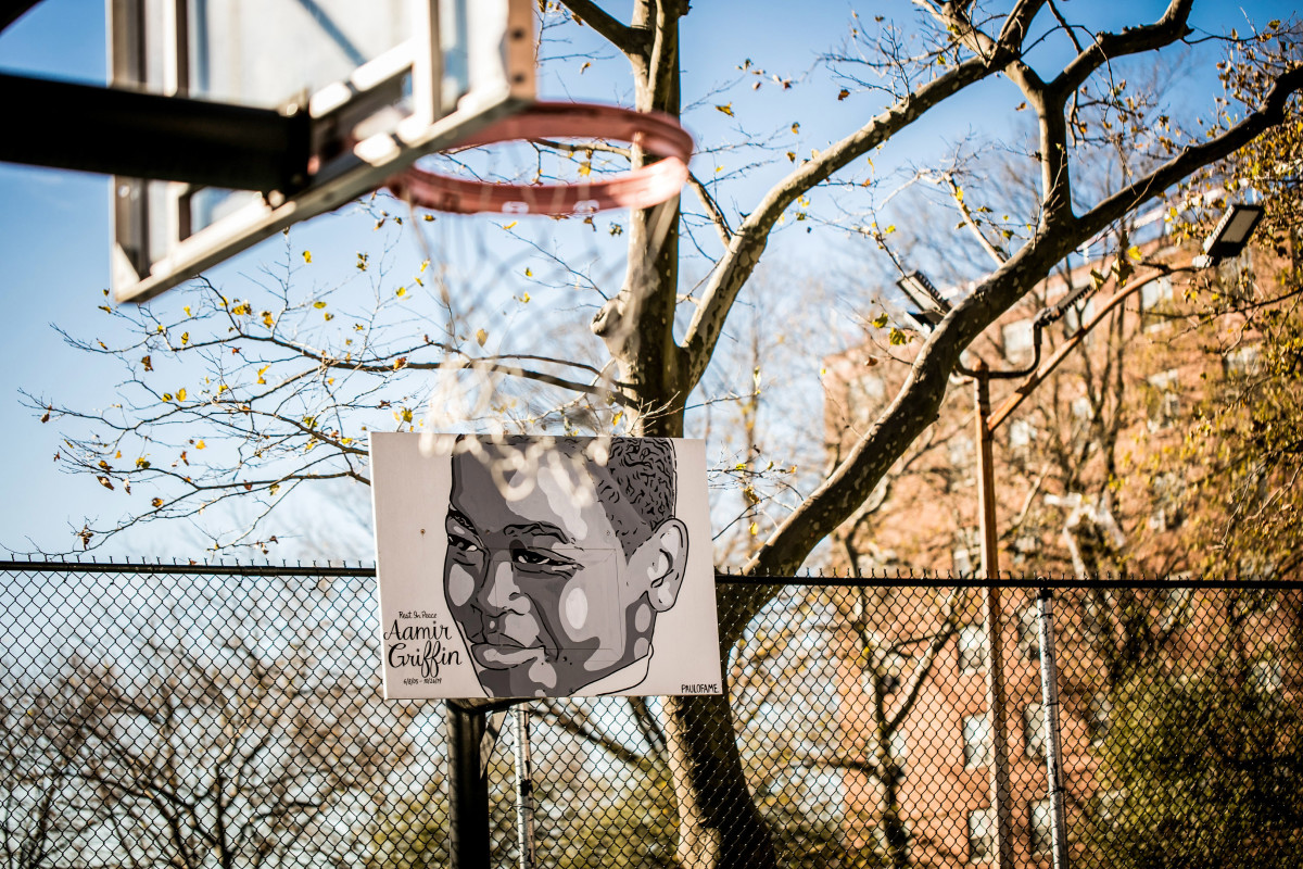 A mural of Aamir Griffin's face spans a backboard at the Baisley Park Houses basketball court.
