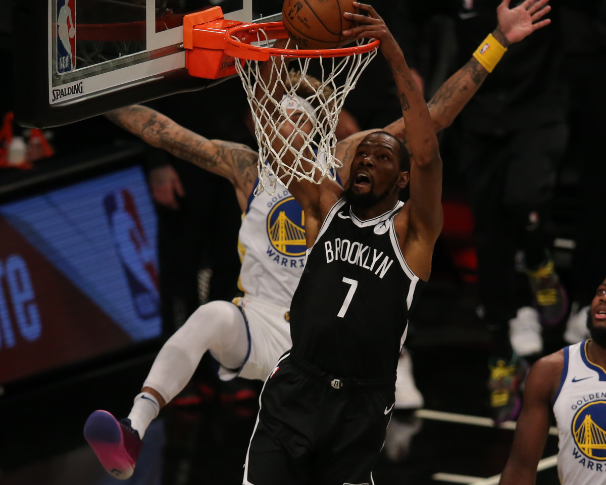 Brooklyn Nets forward Kevin Durant dunks against Golden State Warriors forward Kelly Oubre Jr. during the first quarter at Barclays Center.