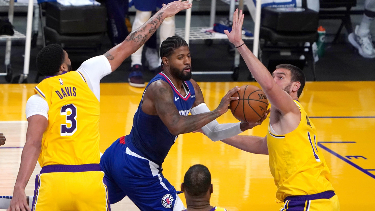 LA Clippers guard Paul George (13) drives against Los Angeles Lakers forward Anthony Davis (3) and center Marc Gasol (14) in the second quarter at Staples Center.