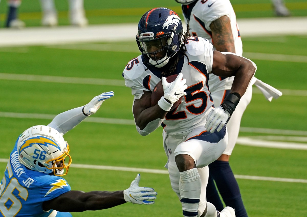 Denver Broncos running back Melvin Gordon (25) runs the ball as Los Angeles Chargers outside linebacker Kenneth Murray (56) attempts to make the tackle during the first half at SoFi Stadium.