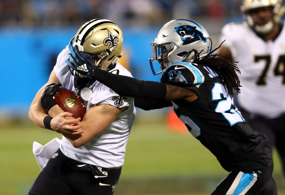 Dec 17, 2018; Charlotte, NC, USA; New Orleans Saints quarterback Taysom Hill (7) gets hit in the face mask by Carolina Panthers cornerback Donte Jackson (26) during the third quarter at Bank of America Stadium. Mandatory Credit: Jeremy Brevard-USA TODAY