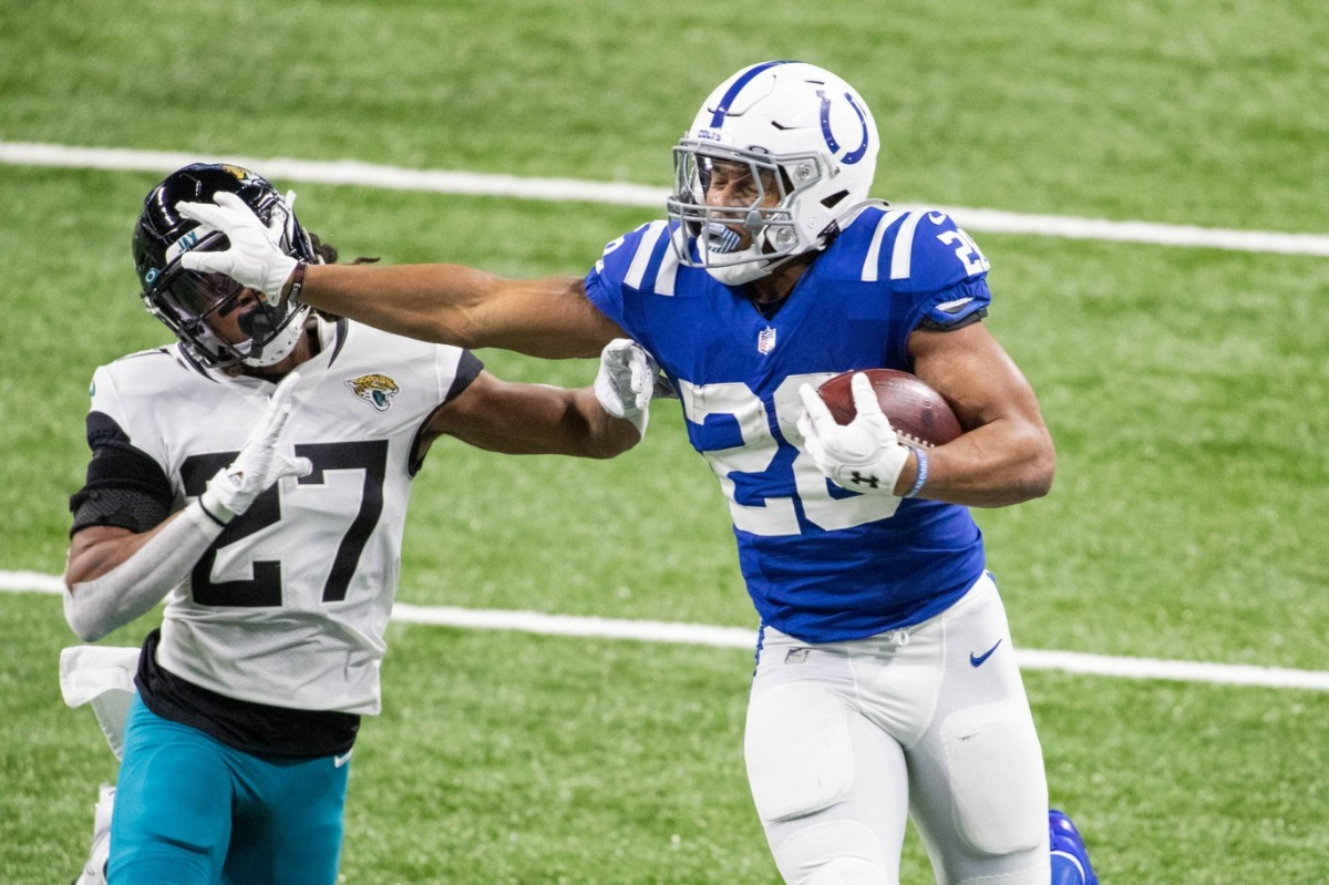Indianapolis Colts rookie running back Jonathan Taylor stiff-arms a Jacksonville Jaguars defender during his franchise-record 253 rushing yards on Sunday.