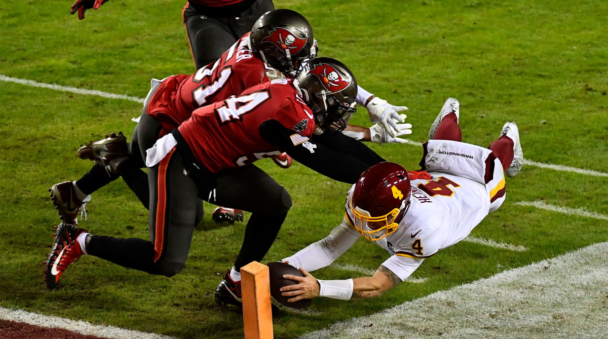 Jan 9, 2021; Landover, Maryland, USA; Washington Football Team quarterback Taylor Heinicke (4) scores a touchdown against the Tampa Bay Buccaneers during the third quarter at FedExField.