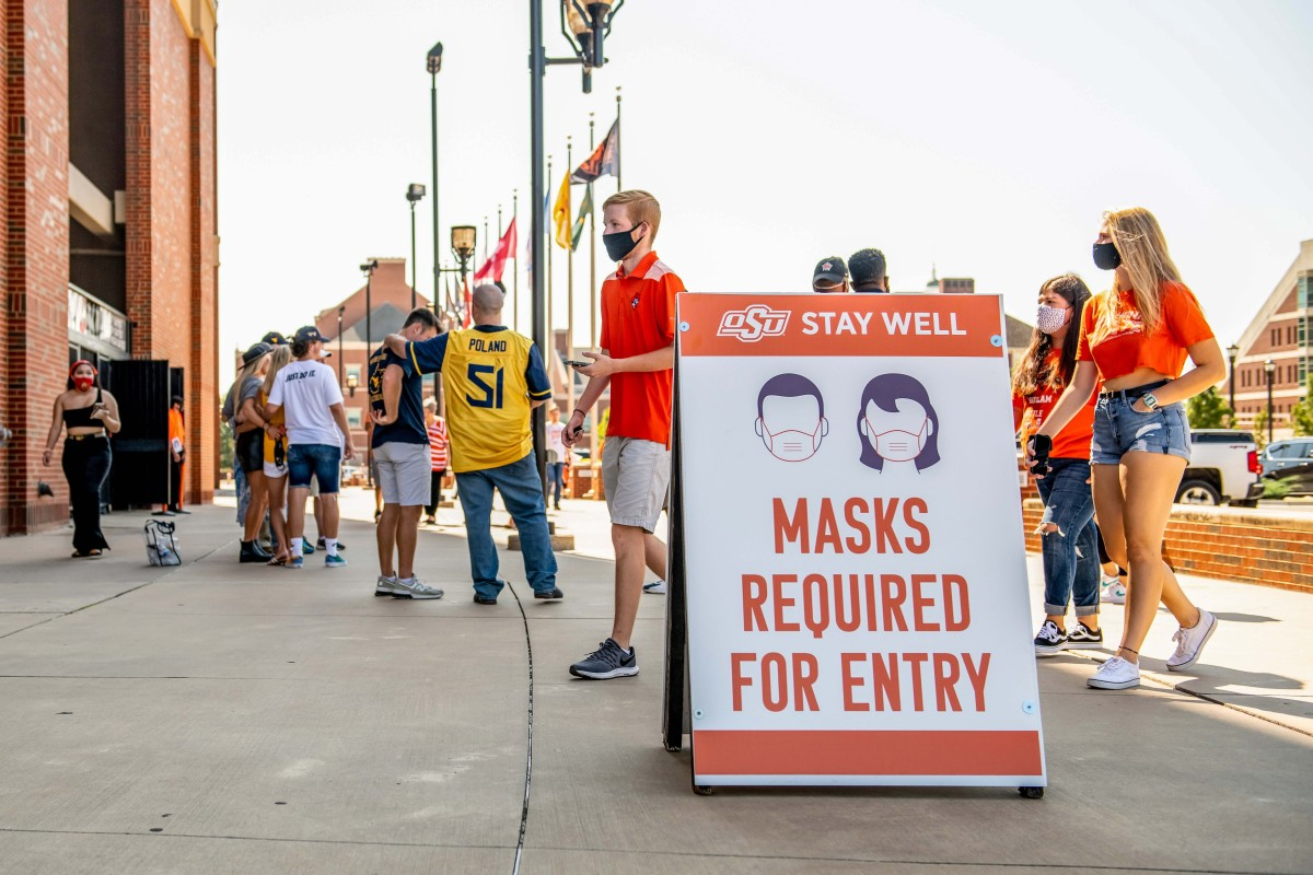 A sign tells fans outside a stadium that masks are required for entry