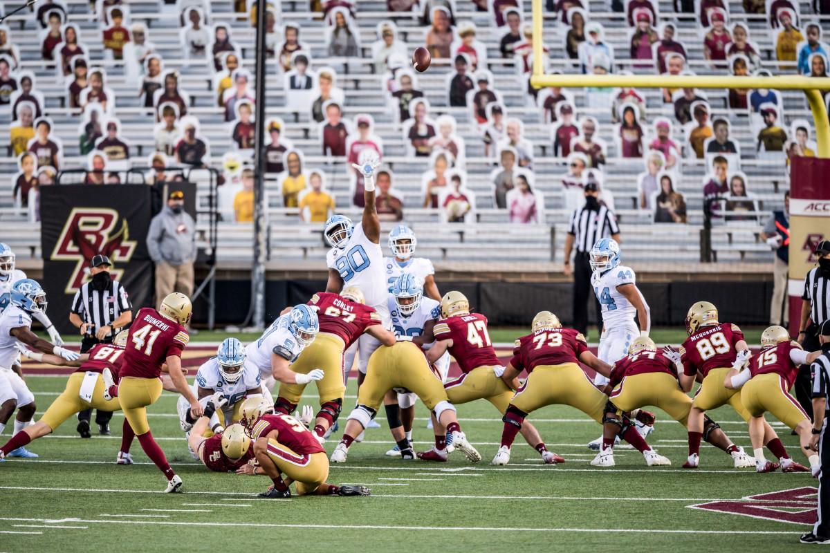 Boston College kicks a field goal as cutouts of fans look on