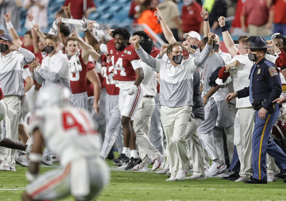 Nick Saban raises his hands in celebration on the sideline