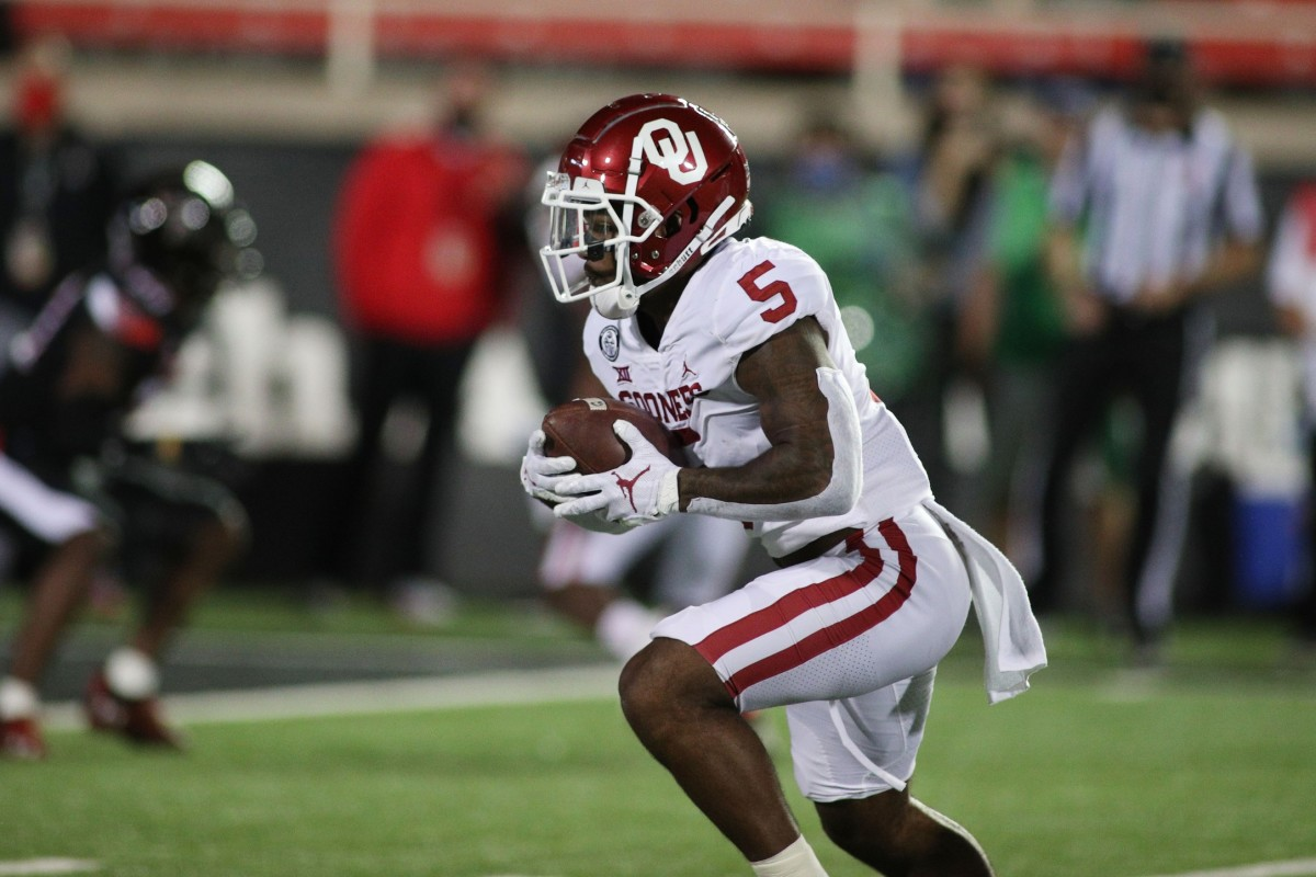Oct 31, 2020; Lubbock, Texas, USA; Oklahoma Sooners running back TJ Pledger (5) rushes against the Texas Tech Red Raiders in the first half at Jones AT&T Stadium.