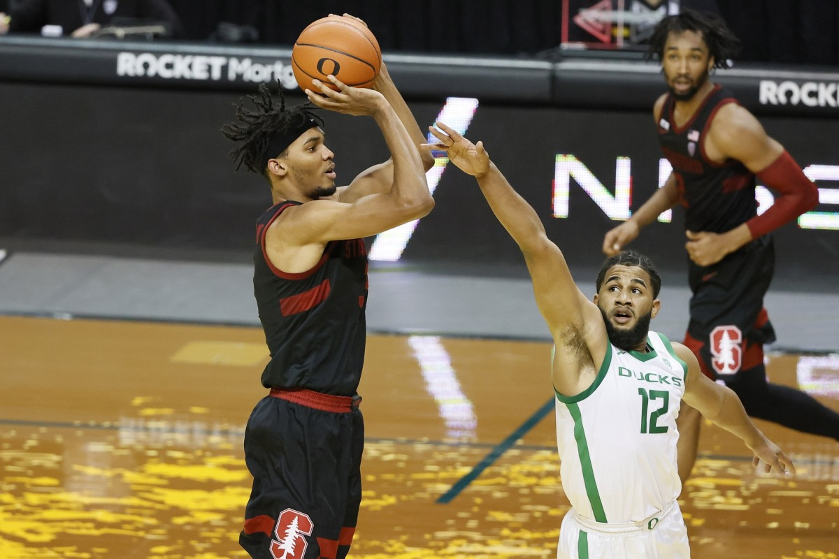 Jan 2, 2021; Eugene, Oregon, USA; Stanford Cardinal forward Ziaire Williams (left) shoots the ball against Oregon Ducks guard LJ Figueroa (12) during the first half at Matthew Knight Arena.