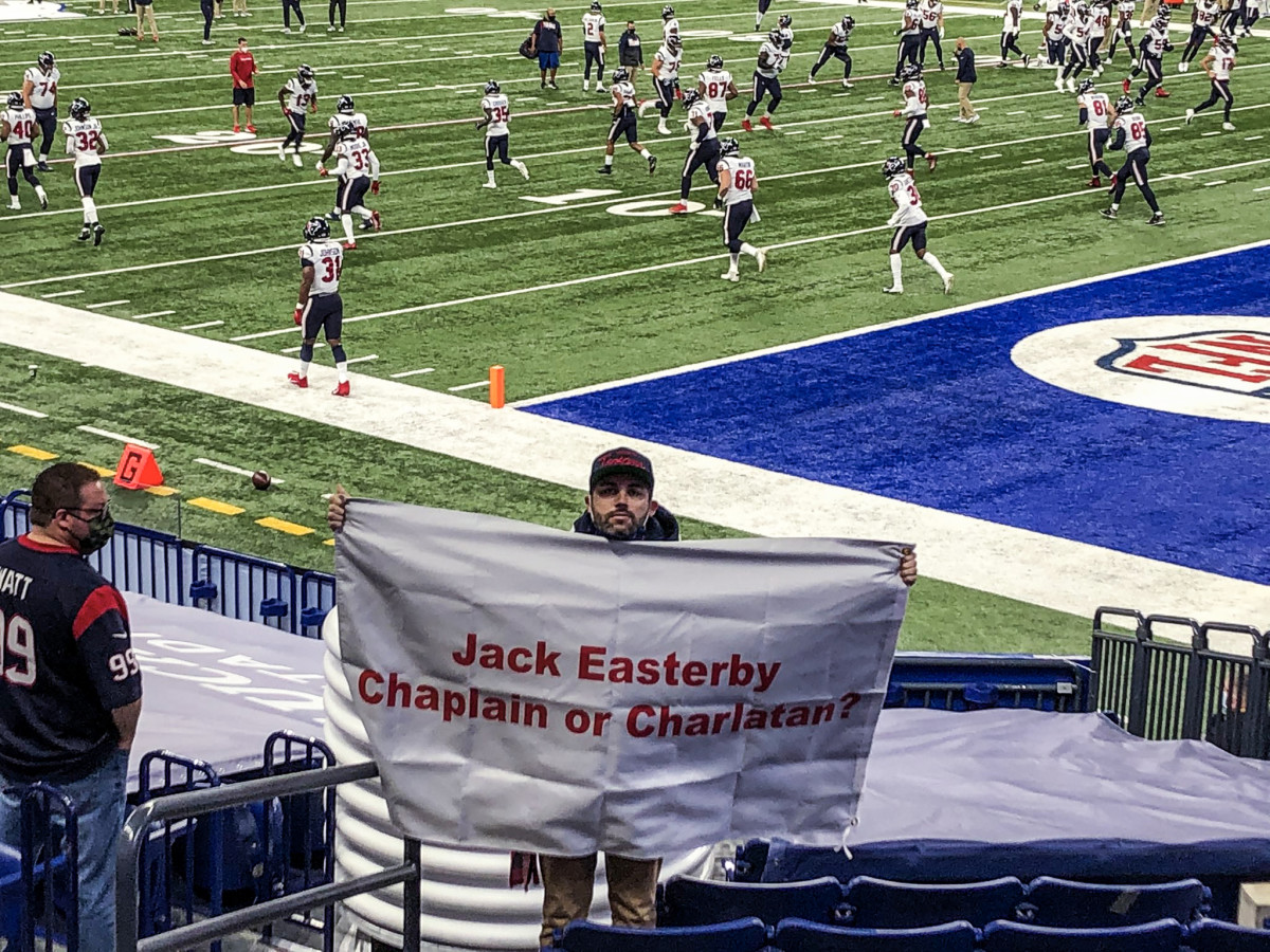 "Texans fan Ronnie Baker holds up a sign—""Jack Easterby Chaplain or Charlatan?""—before a Texans-Colts game"