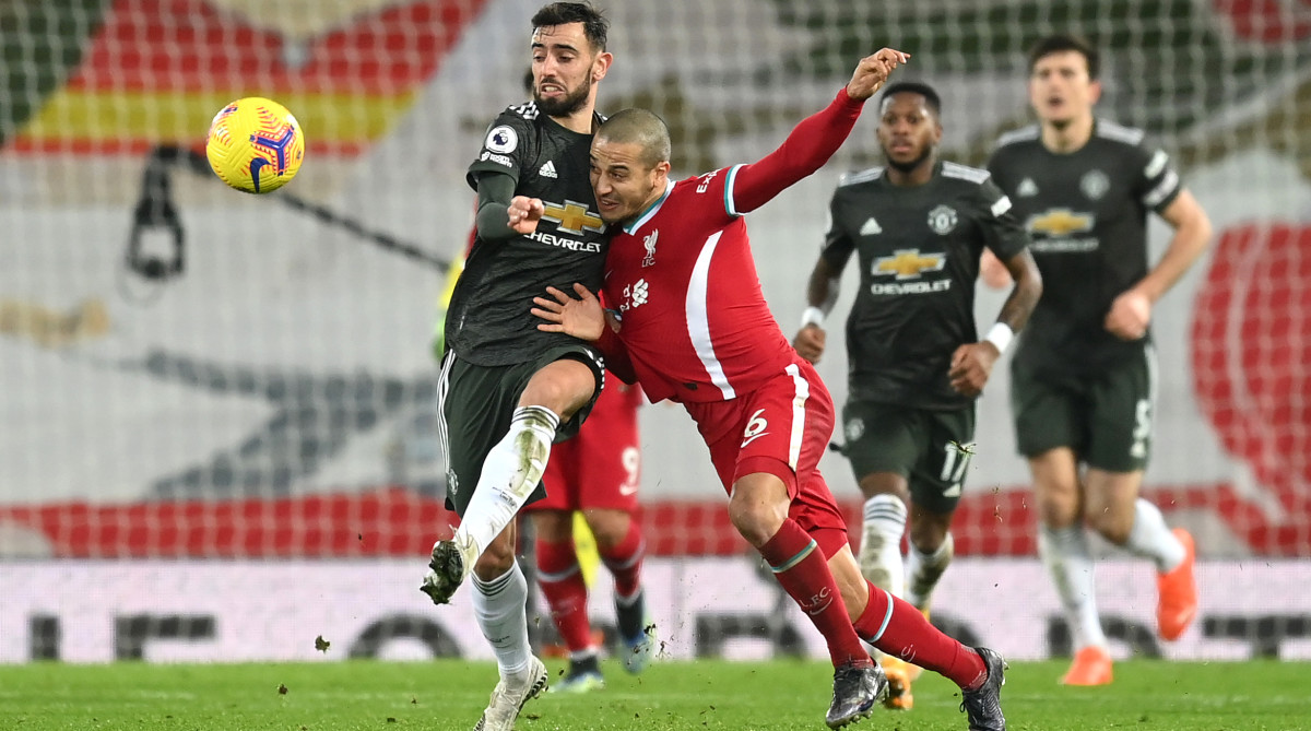 Thiago of Liverpool challenges for the ball with Bruno Fernandes of Manchester United.