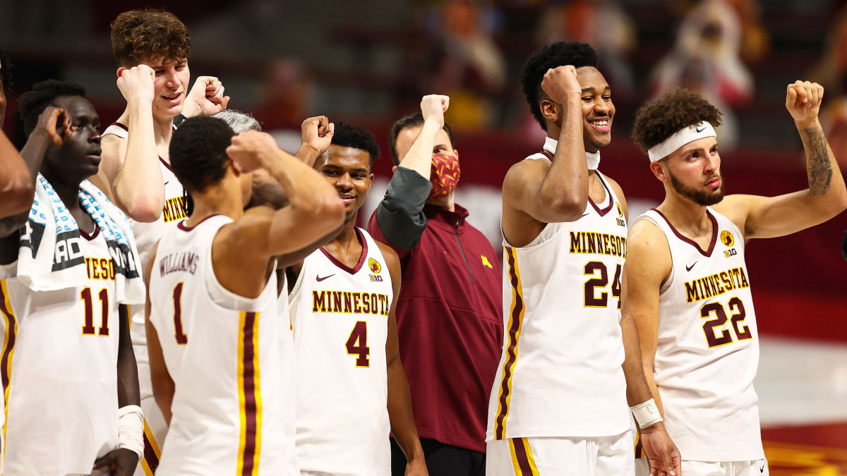 Minnesota basketball players celebrate a win over Michigan