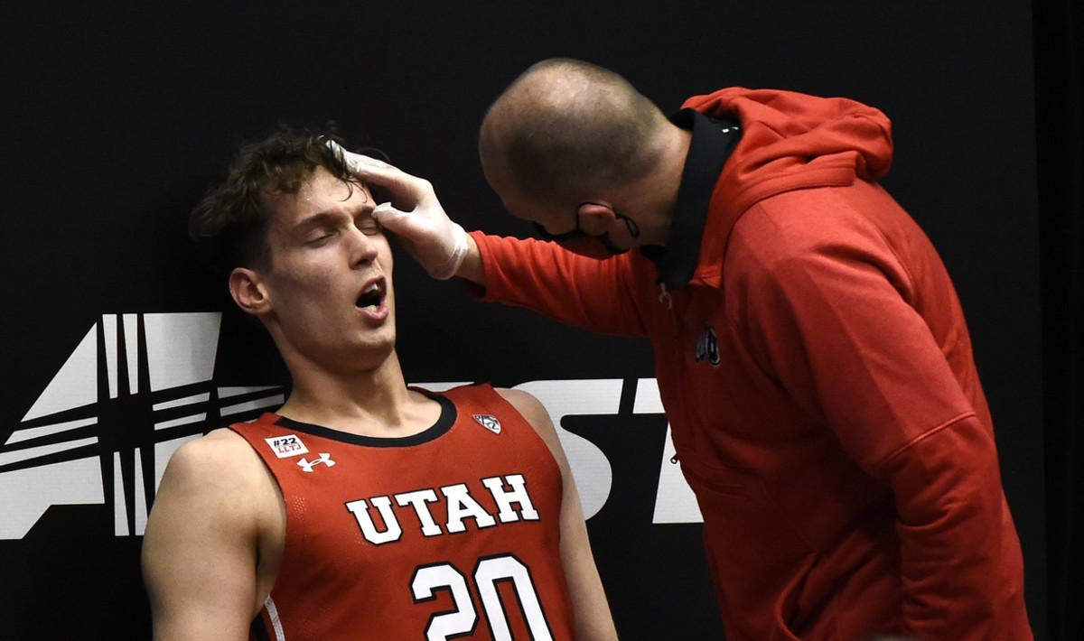 Jan 21, 2021; Pullman, Washington, USA; Utah Utes forward Mikael Jantunen (20) has his left eye checked out by a member of the Utah medical staff during a game against the Washington State Cougars in the second half of a Pac-12 men s basketball game at Friel Court at Beasley Coliseum. Utah won 71-56.