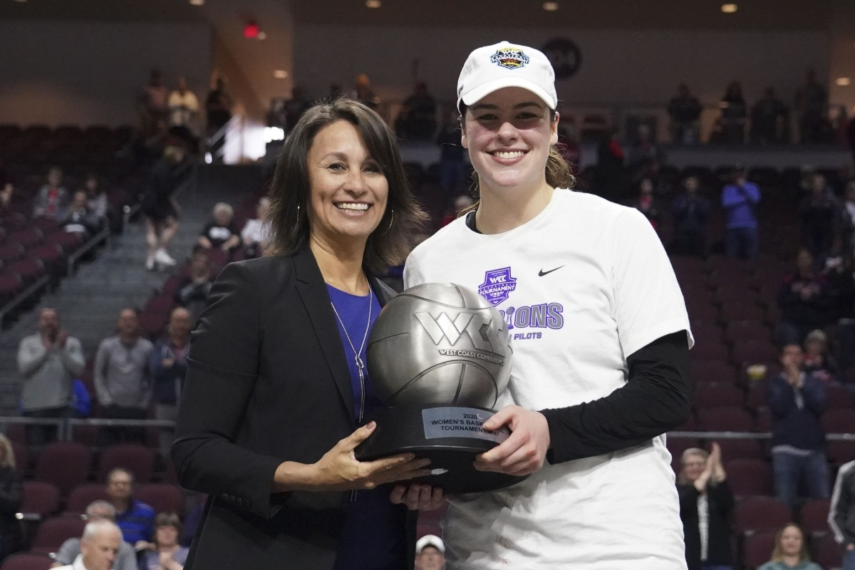 March 10, 2020; Las Vegas, NV, USA; WCC commissioner Gloria Nevarez (left) presents the most outstanding player trophy to Portland Pilots forward Alex Fowler (12) after the championship game in the WCC Basketball Tournament at Orleans Arena.