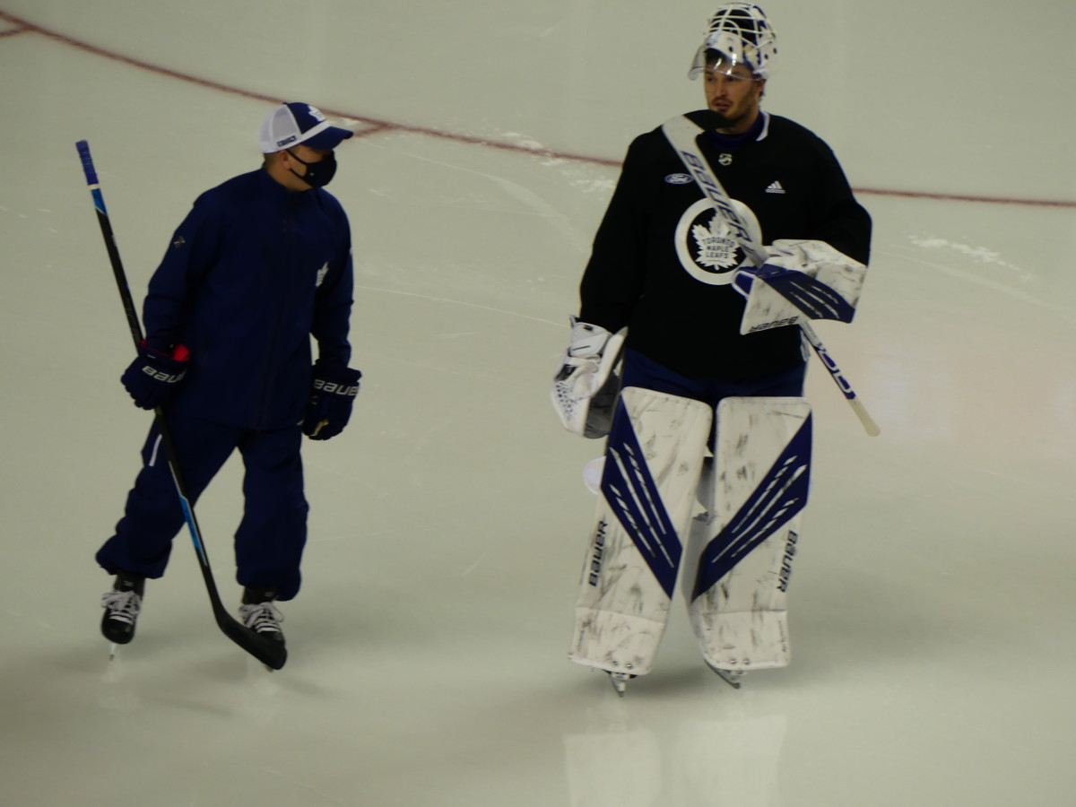 Michael Hutchinson (right) skating with Leafs goaltending coach Steve Briere (left) before practice begins at Scotiabank Saddledome.
