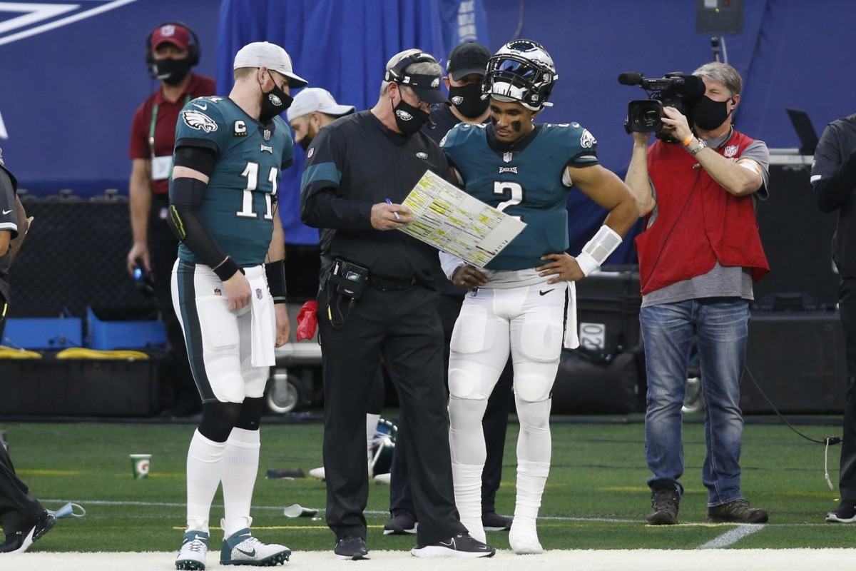 Dec 27, 2020; Arlington, Texas, USA; Philadelphia Eagles quarterbacks Carson Wentz (11) and Jalen Hurts (2) talk with head coach Doug Pederson (C) during a timeout against the Dallas Cowboys in the second quarter at AT&T Stadium.