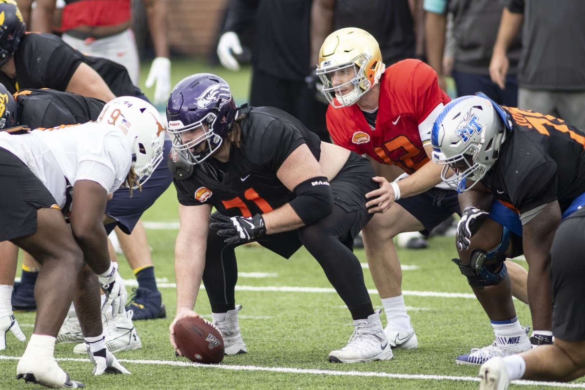 National offensive lineman Quinn Meinerz of Wisconsin -Whitewater (71) gets set with National quarterback Ian Book of Notre Dame (12) in drills during National team practice during the 2021 Senior Bowl week.