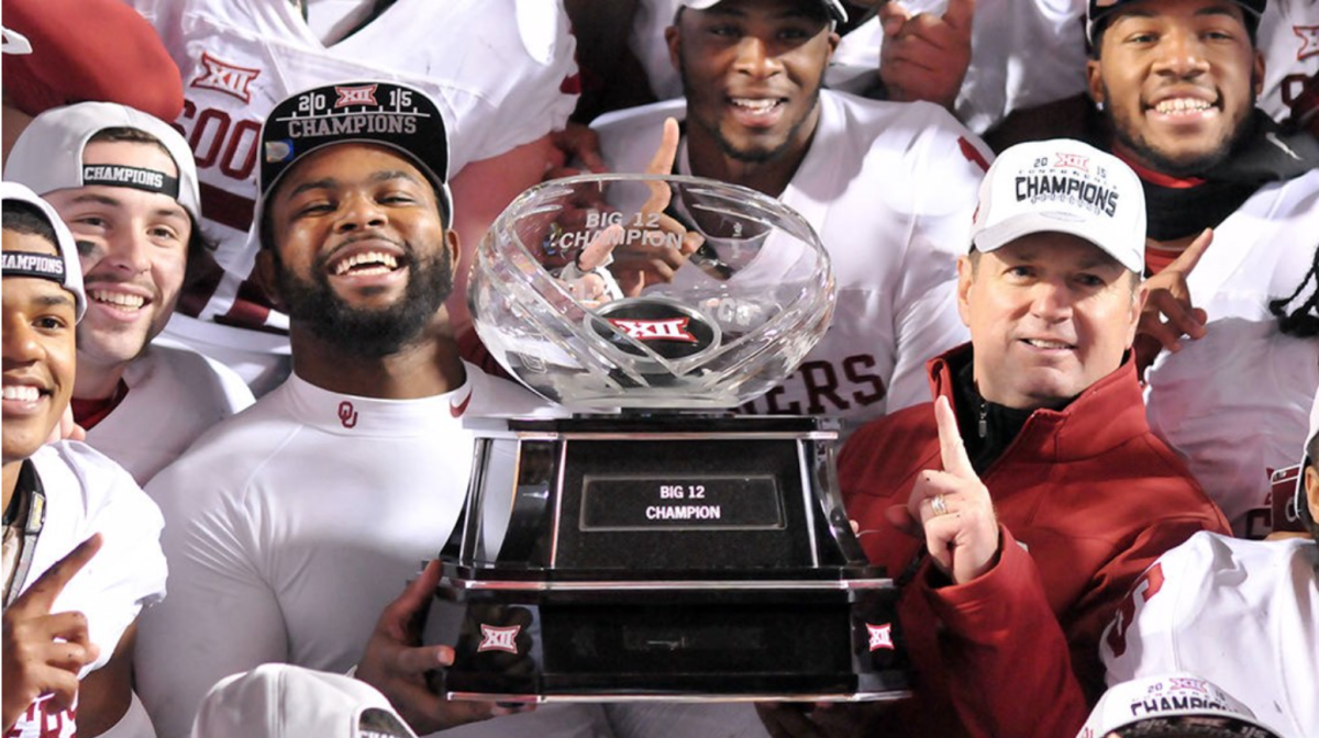 Eric Striker holding the Big 12 Championship Trophy with Bob Stoops