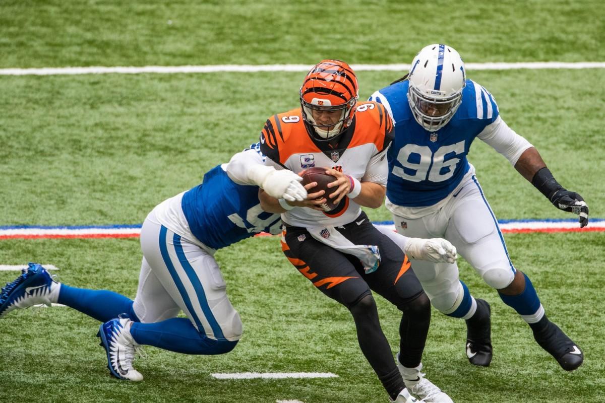 Indianapolis Colts defensive tackle DeForest Buckner (left) and defensive end Denico Autry (96) converge on Cincinnati Bengals quarterback Joe Burrow for a sack.
