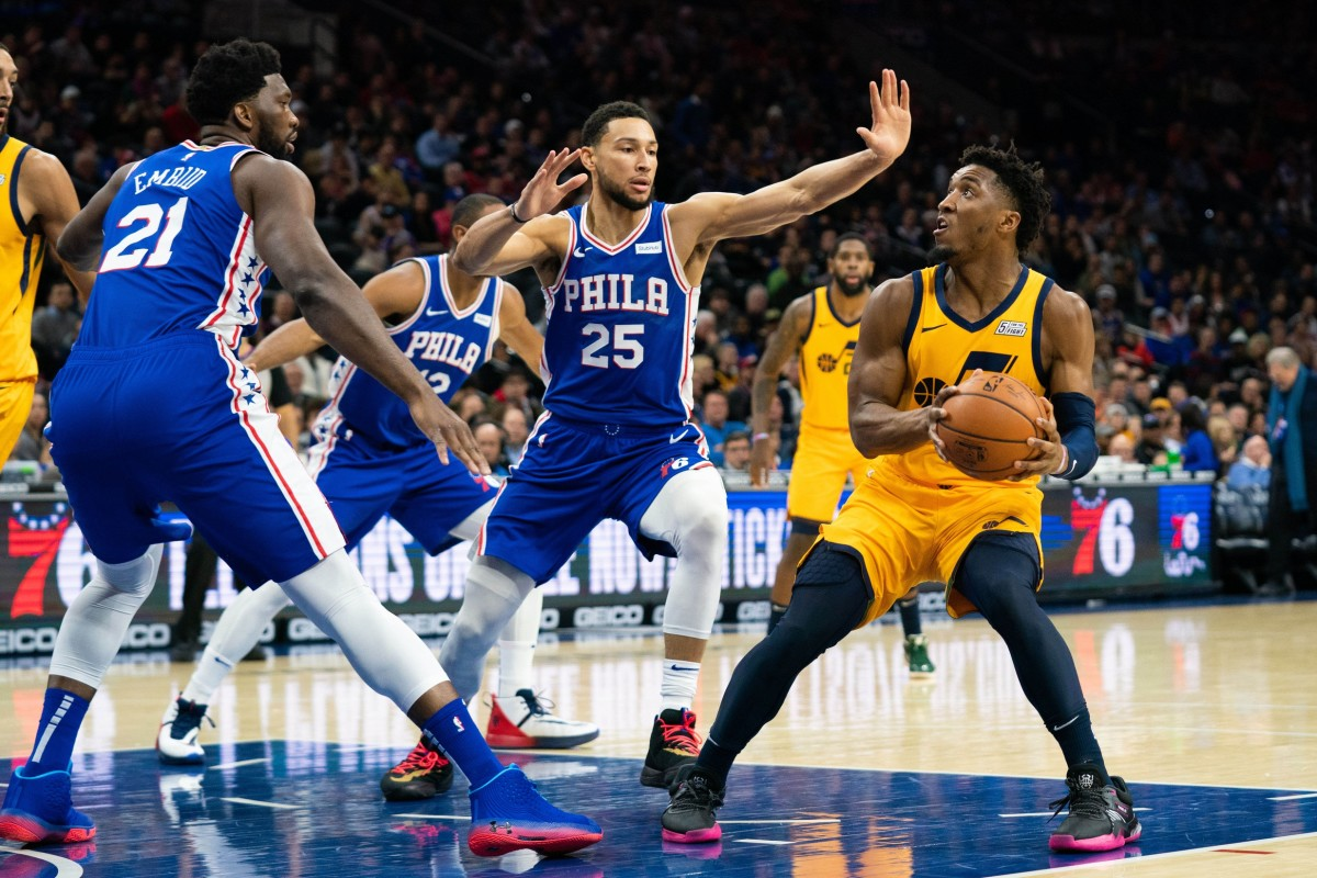 Donovan Mitchell (45) looks to shoot over Ben Simmons (25) and Joel Embiid (21)