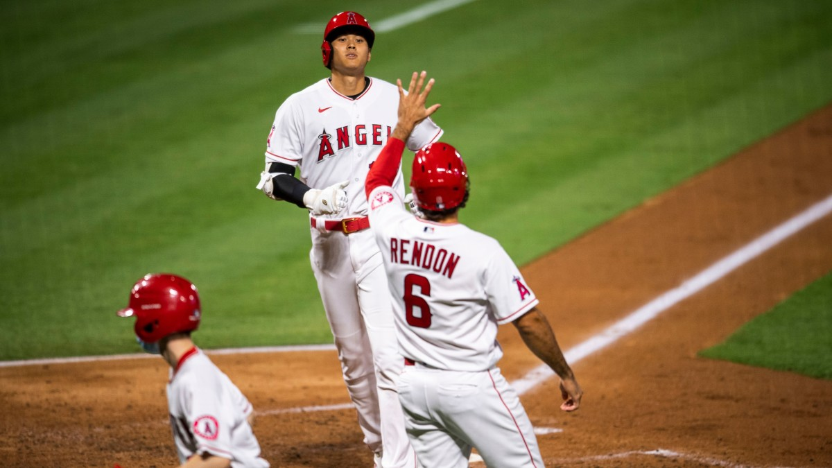 Shohei Ohtani is greeted by Anthony Rendon after scoring a run against the Mariners at Angel Stadium.