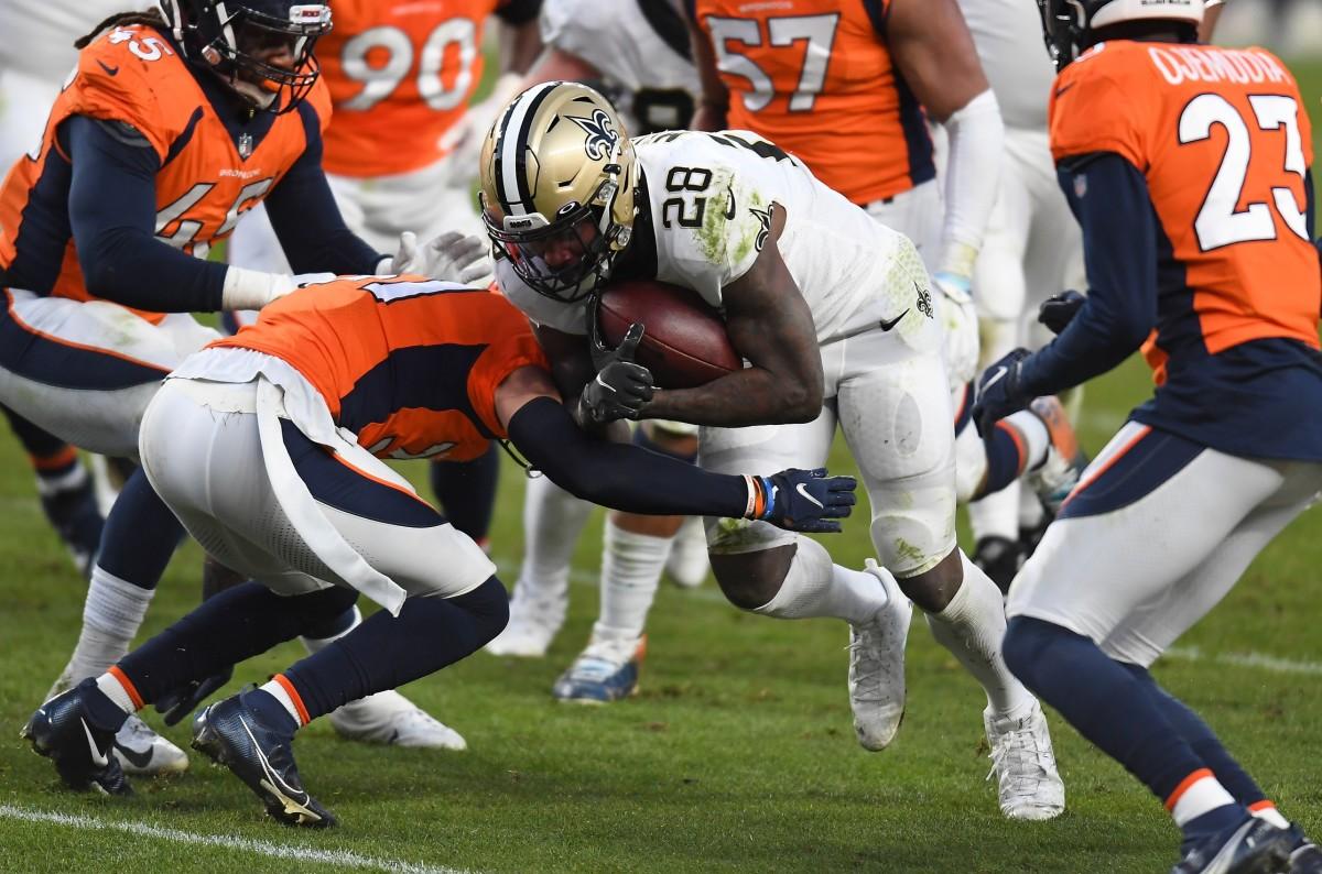 Nov 29, 2020; Denver, Colorado, USA; Broncos free safety Justin Simmons (31) tackles Saints running back Latavius Murray (28) at Empower Field at Mile High. Mandatory Credit: Ron Chenoy-USA TODAY