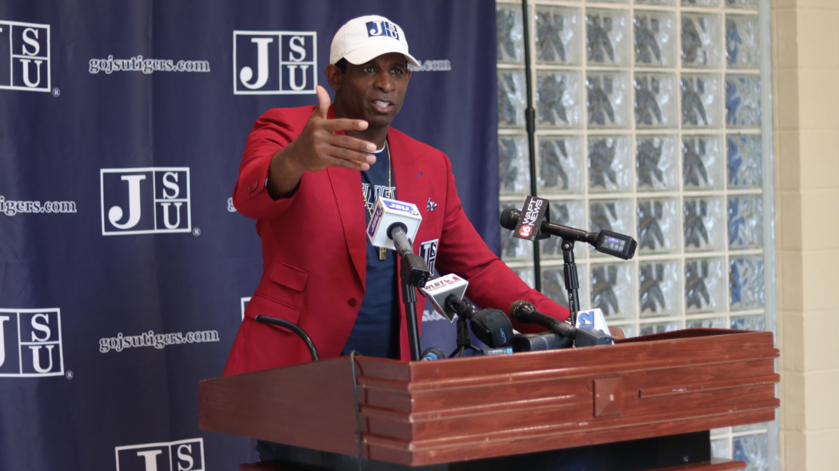 Deion Sanders speaks at a podium after accepting the Jackson State football head coach position.