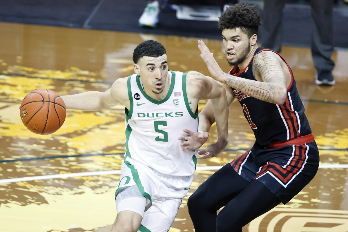 Feb 20, 2021; Eugene, Oregon, USA; Oregon Ducks guard Chris Duarte (5) drives to the basket as Utah Utes forward Timmy Allen (1) defends during the second half at Matthew Knight Arena.
