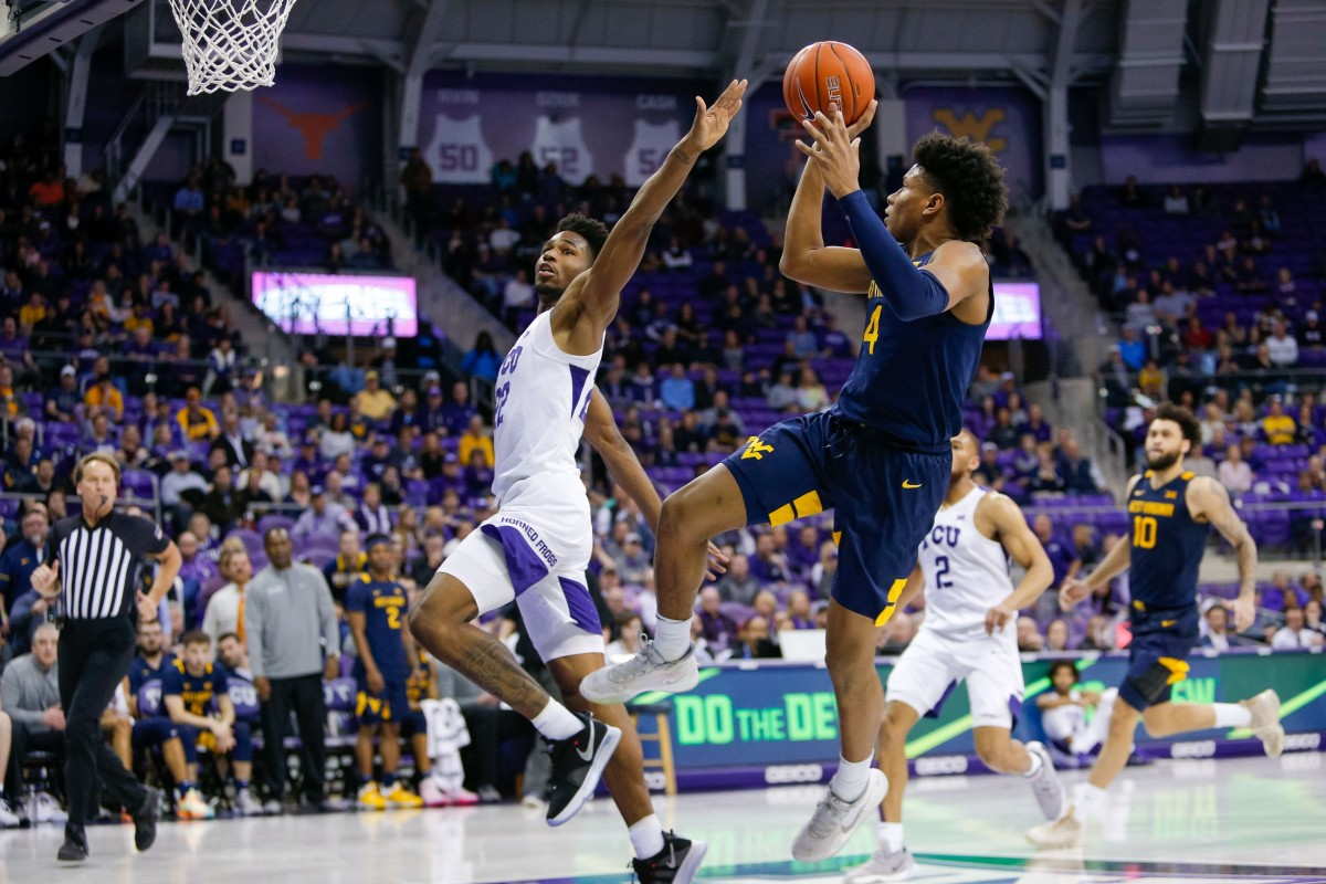 Feb 22, 2020; Fort Worth, Texas, USA; West Virginia Mountaineers guard Miles McBride (4) makes the fade away and is fouled by TCU Horned Frogs guard RJ Nembhard (22) during the second half at Ed and Rae Schollmaier Arena.