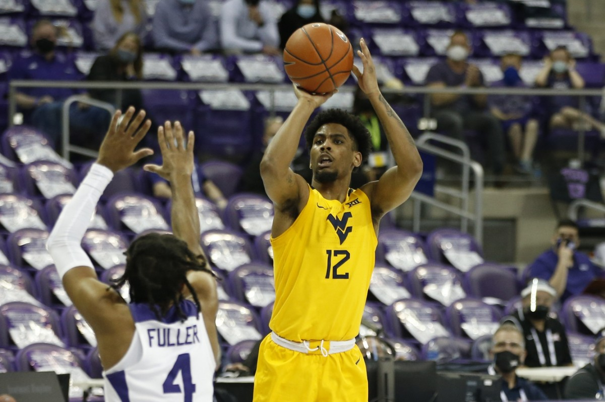 Feb 23, 2021; Fort Worth, Texas, USA; West Virginia Mountaineers guard Taz Sherman (12) shoots against TCU Horned Frogs guard PJ Fuller (4) during the second half at Ed and Rae Schollmaier Arena.