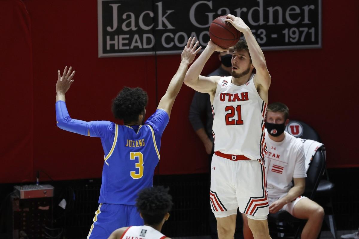 Feb 25, 2021; Salt Lake City, Utah, UCA; Utah Utes forward Riley Battin (21) shoots a three-pointer against UCLA Bruins guard Johnny Juzang (3) in the second half at Jon M. Huntsman Center.